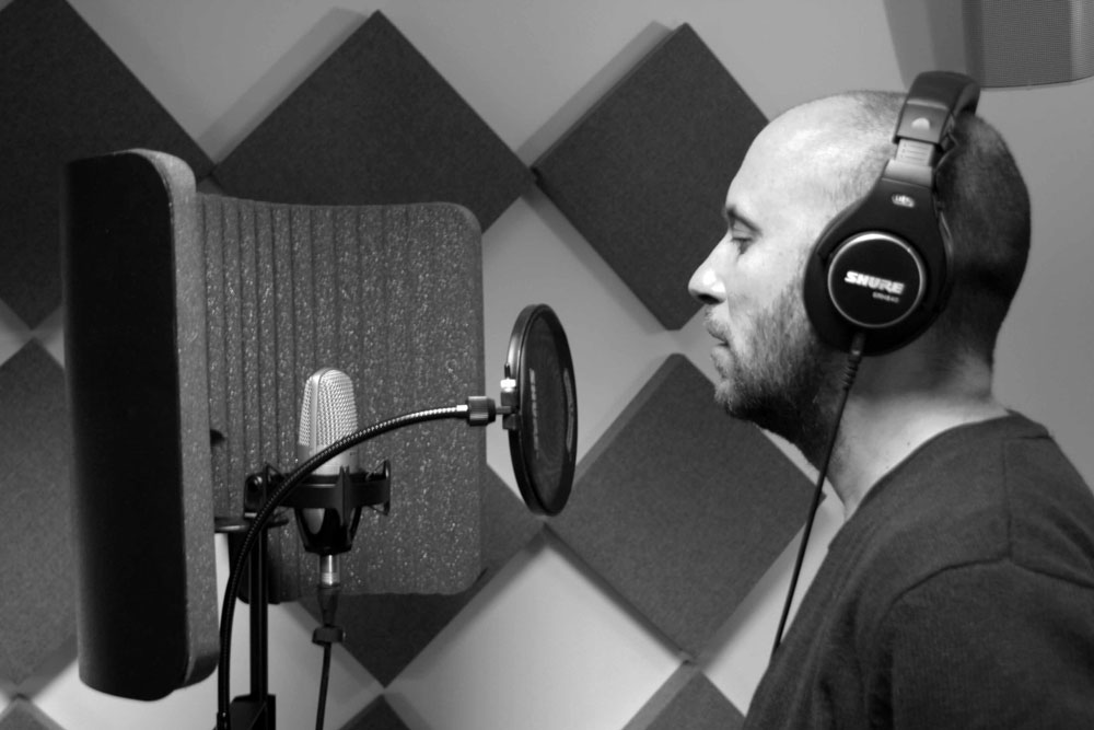 Vocalist in studio with condenser mic and pop filter